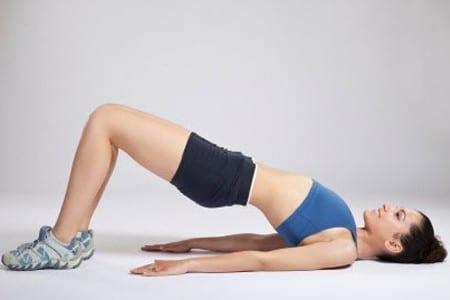 Девушка делает упражнение по поднятию таза