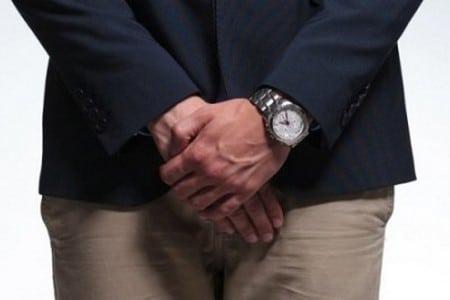 Мужчина прикрывает руками область паха