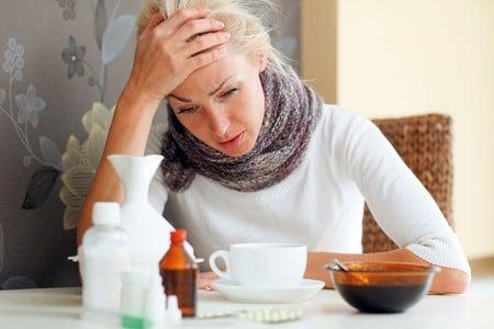 Простуженная женщина сидит за столом