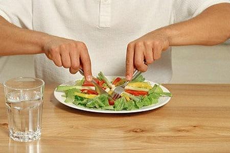Мужчина кушает салат
