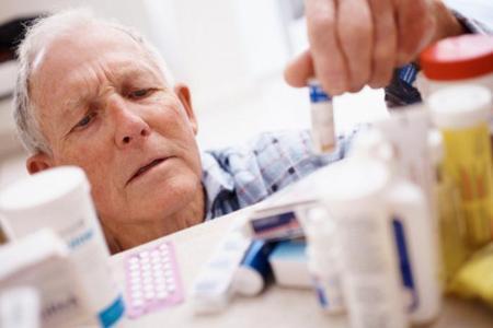 Пожилой мужчина выбирает лекарство