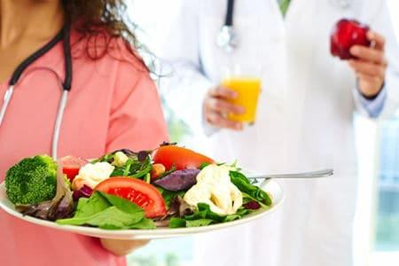 тарелка салата в руках у медсестры