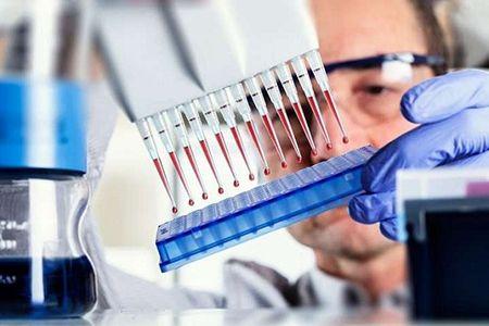 пробирки с кровью в руках у лаборанта