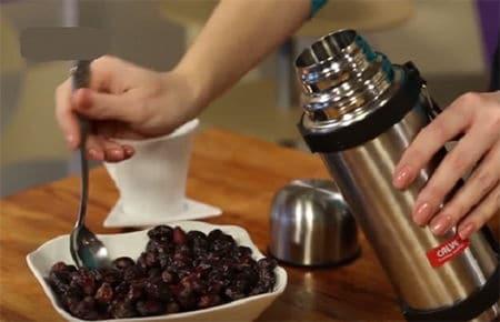 женщина насыпает ягоды в термос