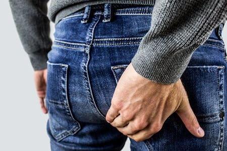 мужчина держится рукой за задний карман