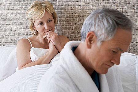 грустные мужчина и женщина сидят на кровати